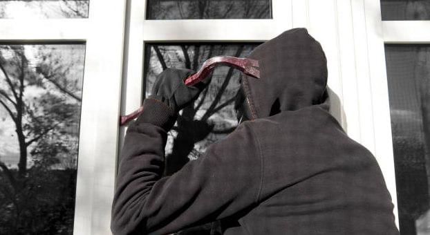 malfaiteur tentant de s'infiltrer dans une maison par une fenêtre non sécurisée